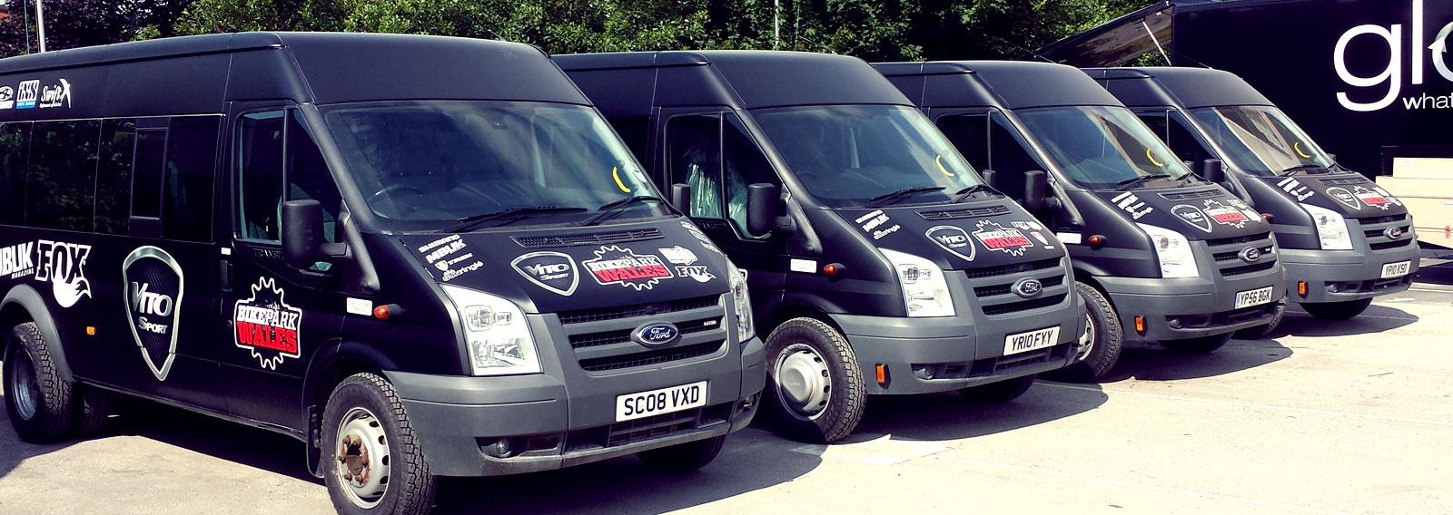 fleet of black vans with custom graphics