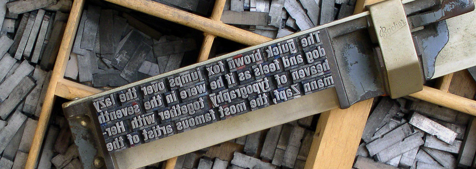 old fashioned letterpress block with selection of letter tiles in wooden trays